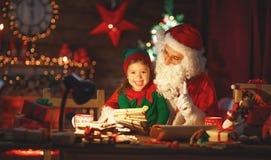 Santa Claus czyta list mały elf choinką Fotografia Royalty Free