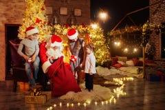 Santa Claus dá presentes às crianças no dia de Natal fotos de stock