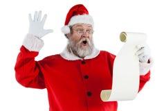 Santa Claus danandeansiktsuttryck, medan läs-, bläddrar Fotografering för Bildbyråer
