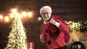 Santa Claus dancing with bag of gifts. Delivery christmas gifts. Positive human facial expressions and emotions.