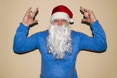 Santa Claus dancing on a light background. He celebrates Christmas after hard work. royalty free stock image