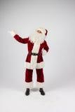 Santa Claus dans des lunettes et le costume rouge font une remarque avec des mains Photos stock