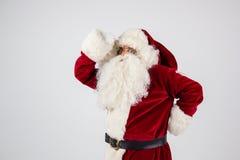 Santa Claus dans des lunettes et le costume rouge font une remarque avec des mains Photo stock