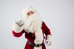 Santa Claus dans des lunettes et le costume rouge font une remarque avec des mains Images stock