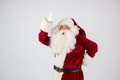 Santa Claus dans des lunettes et le costume rouge font une remarque avec des mains Photo libre de droits