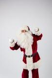 Santa Claus dans des lunettes et le costume rouge font une remarque avec des mains Photographie stock