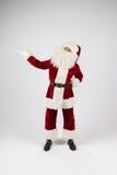 Santa Claus dans des lunettes et le costume rouge font une remarque avec des mains Photos libres de droits