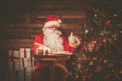 Santa Claus dans l'intérieur à la maison en bois Photographie stock libre de droits
