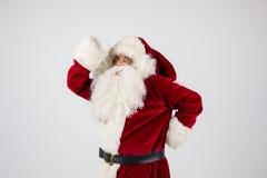 Santa Claus dans les lunettes et le costume rouge a mis des mains sur la tête Photos stock