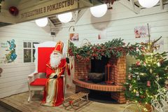 Santa Claus dans sa maison se reposant dans sa grande chaise rouge près d'une cheminée photos stock