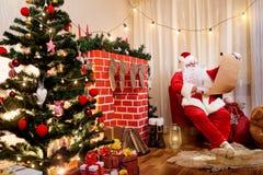 Santa Claus dans une liste de Noël avec un cadeau dans les mains du Photo libre de droits