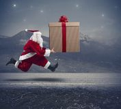 Santa Claus de funcionamiento con el regalo grande Imagen de archivo libre de regalías