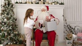 Santa Claus-de holding stelt en koesterend een weinig leuk meisje voor stock video