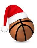 Santa Claus de port sur une boule de basket-ball Images stock