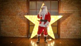 Santa Claus-de rotsster, danst, zingt grappige Kerstmisliederen in retro microfoon stock footage