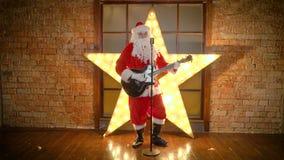 Santa Claus-de rotsster, spelengitaar, zingt grappige Kerstmisliederen in retro microfoon stock videobeelden