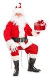 Santa Claus de sourire sur une chaise tenant un actuel images libres de droits