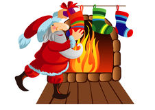 Santa Claus is decomposed gifts in socks. That hang over the fireplace Royalty Free Stock Images