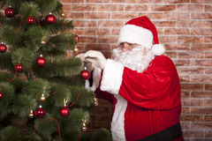 Santa Claus decorates Christmas tree Royalty Free Stock Photos