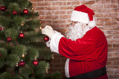 Santa Claus decorates Christmas tree Royalty Free Stock Photography