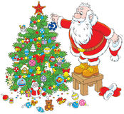 Santa Claus decorating a Christmas tree Royalty Free Stock Photography