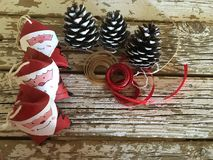 Santa claus decoration with pine cones and red and gold ribbons on wood Royalty Free Stock Photography