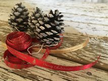 Santa claus decoration with pine cones and red and gold ribbons on wood Royalty Free Stock Photo
