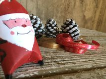 Santa claus decoration with pine cones and red and gold ribbons on wood Stock Photography