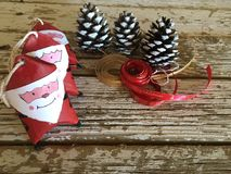 Santa claus decoration with pine cones and red and gold ribbons on wood Royalty Free Stock Photos