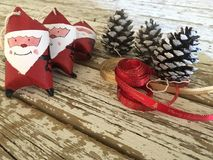 Santa claus decoration with pine cones and red and gold ribbons on wood Stock Images