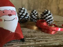 Santa claus decoration with pine cones and red and gold ribbons on wood Royalty Free Stock Images