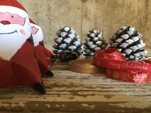 Santa claus decoration with pine cones and red and gold ribbons on wood Stock Photos
