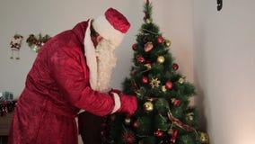 Santa Claus dekorerar en julgran stock video