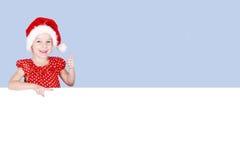 In Santa Claus del cappuccio la ragazza mostra un dito eccellente e sullo spazio di pubblicità Fotografia Stock Libera da Diritti