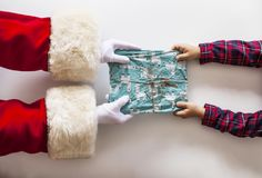Santa claus delivering a gift to a child stock photo