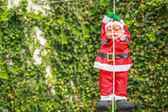 Santa claus descending from a rope in a yard. In a village house Royalty Free Stock Images