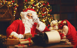 Santa Claus at desk with letters,   gifts near Christmas tree Royalty Free Stock Images