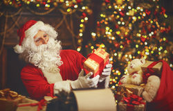 Santa Claus at desk with letters,   gifts near Christmas tree Stock Image