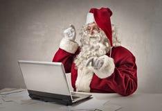 Santa Claus, die auf der Tastatur schreibt Lizenzfreie Stockfotografie
