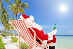 Santa Claus, die auf einem Stuhl und einem trinkenden Bier, auf einem Strand liegt Stockbild