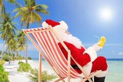 Santa Claus, die auf einem Stuhl und einem trinkenden orange Cocktail liegt Stockbild