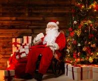 Santa Claus, die auf Schaukelstuhl sitzt Lizenzfreie Stockfotos