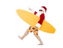 Santa Claus, die Brandungsbrett mit dem Zeigen von Geste hält Stockfotografie