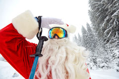 Santa Claus die in de bergen op sneeuw in de winter in Christm ski?en stock foto's