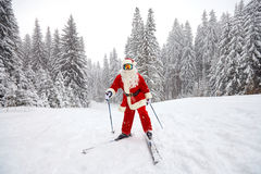 Santa Claus die in de bergen op sneeuw in de winter in Christm ski?en stock afbeelding