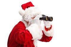 Santa Claus, die durch Ferngläser schaut Stockbilder