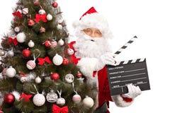 Santa Claus die een film houdt clapperboard Stock Foto