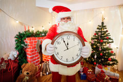 Santa Claus die een horloge in zijn hand houden, die op de klok a richten stock foto