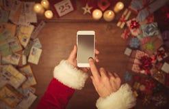 Santa Claus die een slimme telefoon met behulp van Stock Foto