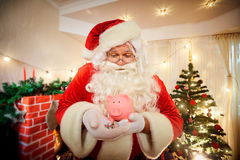 Santa Claus die een varkensspaarvarken en muntstukken in Kerstmis houden stock foto